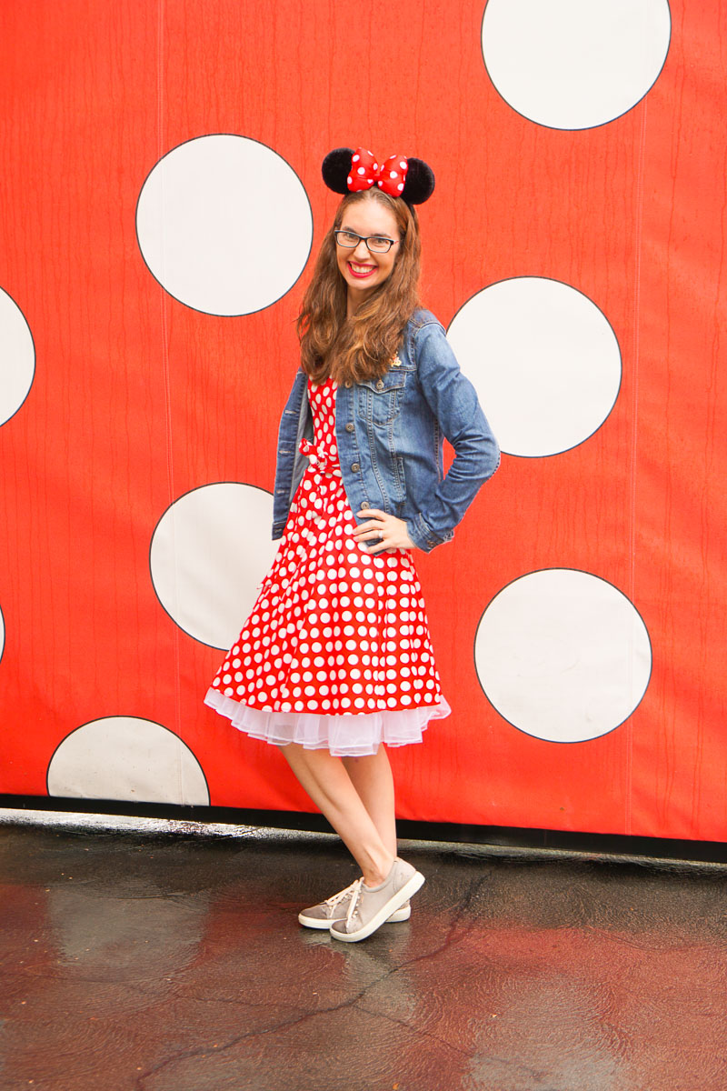 What to Do at Disneyland in the Rain, tips featured by top US Disney blogger, Marcie and the Mouse: A woman dressed in a red polka dot dress wearing Minnie ears standing in front of a polka dot wall at Disneyland