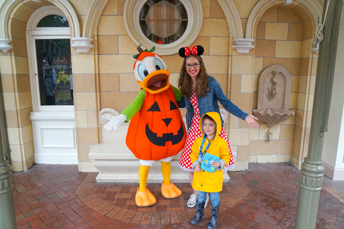What to Do at Disneyland in the Rain, tips featured by top US Disney blogger, Marcie and the Mouse: Donald Duck dressed as a pumpkin posing with a mom and preschooler at Disneyland