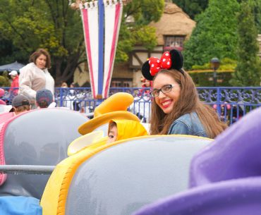 What to Do at Disneyland in the Rain, tips featured by top US Disney blogger, Marcie and the Mouse: Mom and boy sitting in the Dumbo ride at Disneyland in the rain
